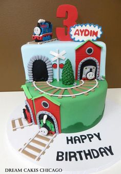 I thought that this picture gives you a good angle of the cake coming out of the bottom layer so that you can see how they do it. You could just use the green train (bottom layer) for the train coming out of tunnel and Thomas (who is on top) for the additional train on the tracks along the cake board.