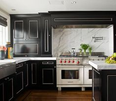 Carrara White marble countertops and full height backsplash with black cabinets