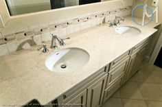 This double sink vanity uses Botticino Fiorito marble to match the tan color scheme of cabinets and tile.