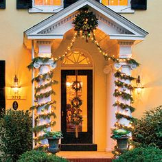 Play up the architecture of your home by accentuating features, like the stately columns flanking this front porch, with spiraling garland and bright Christmas lights.
