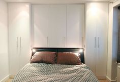 Clean contemporary fitted wardrobe painted semi matt white. Integrated bedside lights.     This wardrobe was designed form scratch to fit this space exactly.
