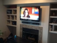 TV mounting over a fireplace with wires concealed in the wall and ...