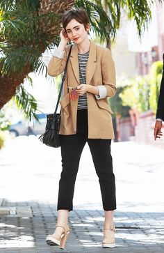 Lily Collins wears a striped top, camel blazer, sleek black cropped trousers, nude and white heels, and a black tassel bucket bag