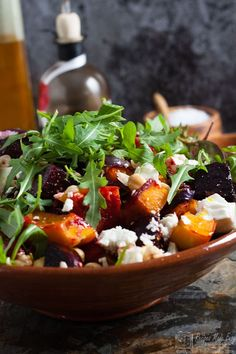 bowl of beetroot, squash and feta salad with oil and vinegar in background