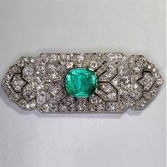 Broche plaque des années 1920 ornée d'une importante émeraude de forme coussin au centre d'un pavage de diamants. Poids de l'émeraude : 8 ct environ.