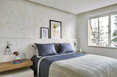 Quarto com cama de casal, forro de gesso com spot embutido e uma das paredes de tijolinho aparente descascada e pintada de branco. Decoração de Apartamento em Higienópolis, São Paulo