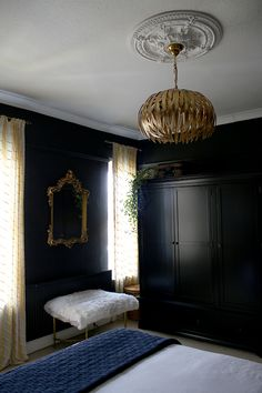 black bedroom wardrobes with gold light fixture and ornate gold mirror - see more on www.swoonworthy.co.uk