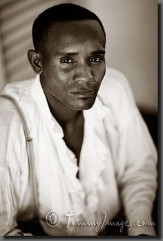 An Afro-Cuban man in colonial attire    Keywords: Stock Photo Picture Cuba Cuban Spanish Speaking Countries Latin America Trinidad Sancti Spíritus Vertical Timeless Afro-Cuban Black Male History 20-30 Years Old Adult Black Man Black Person Looking Into Camera Latin American Art Torso Sancti Spiritus African Descent Colonial Attire Clothing Male Sepia Toned Portrait