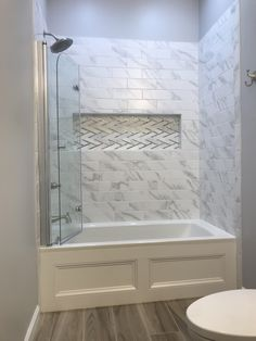 Shower tub combo. Dreamline shower door. Marble tile with glass and marble niche. Wainscoting around tub. Wood loom tile.
