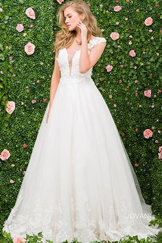 Beautiful floor length ivory wedding ballgown with cap sleeves and plunging v neckline features floral appliques on the hemline and bodice.