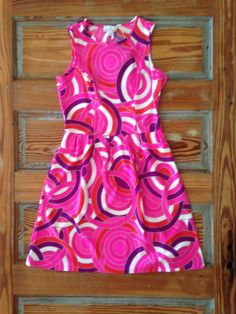 We are in love with our new shipment of Jude Connally dresses, like this hot pink sleeveless A-line with swirls galore! It's right on target for spring.