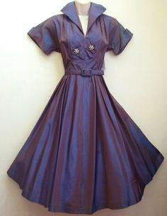 1950's evening dress in stunning two-tone taffeta of purple/mauve/blues. Semi fitted to the waist, it has a classic wide collar and cuffs, with rhinestone and pearl flower detail to the chest. Beautiful falling skirt with self-fabric belt. No maker label.