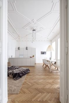 herringbone floors, white living room / kitchen open plan high ceiling