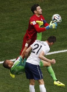 France's goalkeeper Hugo Lloris (top) makes a save near teammate Laurent Koscielny (21) and Nigeria's Peter Odemwingie during their 2014 Wor...
