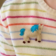 Unicorn brooch with blue tail and mane, made from felt and measures approx 8 cm across.
