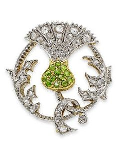 An early 20th century demantoid garnet and diamond thistle brooch. Of openwork circular form, the bud set with demantoid garnets, the flowerhead and foliage set with rose-cut diamonds, the reverse with a hook for a drop.