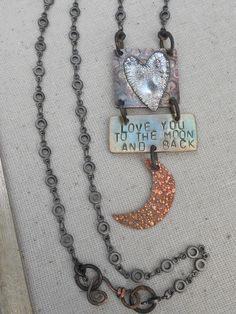 Sterling silver heart on copper, brass phrase plate and copper moon. All pieces designed by Angela Gruenke/Contents Jewerly
