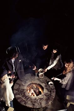 Friends gathering around a stone firepit roasting hand-crafted marshmallows for s'mores #bonfire #party