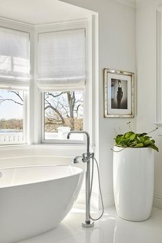 A soaking tub in a bay window is paired with a floor mount tub filler next to a tall glossy planter under an Audry Hepburn wall art.