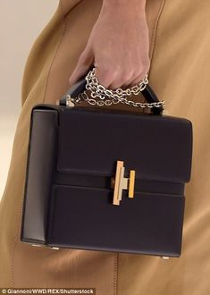 A gleaming deep brown leather Cinetic d'Hermes bag comes with a chain strap and distinctive gold clasp