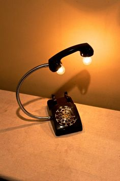 This is one of my favorite lamps to make. I start with a vintage rotary phone, replace the cord with a chrome gooseneck, add candelabra sockets into the mouth and ear piece and Voila! you have yourself a totally unique desk lamp or bed-side light. Ive wired it with a twisted wire cloth covered, an in-line switch, and a reproduction button style plug. This particular phone is black but I could lampify any old rotary phone. If you happen to have one and would like it converted, please let me…