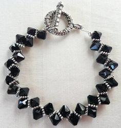"This one-of-a-kind ""Zipper"" bracelet features jet-black 6mm Swarovski bicone top-drilled crystals interspersed with silver-plated 5mm square beaded spacers which form a unique zipper pattern. The piece is finished with an antiqued silver-plated round toggle clasp. The bracelet measures 6.5 inches.  http://www.etsy.com/listing/94913678/jet-black-swarovski-crystals-zipper"