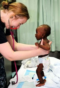 This is a photo of a woman treating a baby in Zambia. This missions group put together health clinics in some villages to test the people for diseases, and to help children become fully healthy.