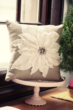 DIY pillow with felt flowers petals and jingle bell center - use a vintage brooch for the center