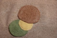 How to creatively repair moth holes in your favorite sweaters using felted sweater scraps.