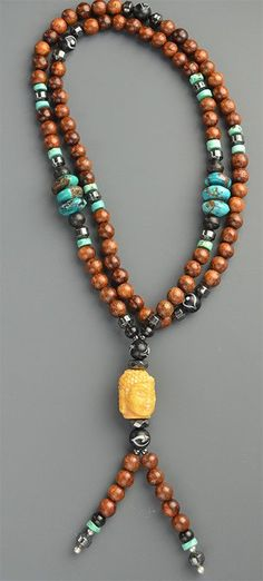 Beautiful handmade Mala necklace, with dark wood beads, Chinese turquoise beads, hematite spacers, and newly-made black and white eye beads. The center bead is a large carved bone Buddha head. The woo