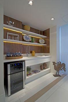 O apartamento tem espaços diferenciados com funções múltiplas. A varanda é um bom exemplo disso, no mesmo ambiente ficam localizados o espaço gourmet e a área de descanso. A iluminação direcionada destaca as prateleiras, o painel de madeira e os objetos decorativos. A moderna adega completa o décor sofisticado do ambiente.