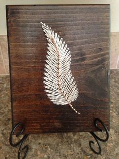 A simple feather that is beautifully handcrafted and strung. A 7x9 (approx.) string art feather board Standard board is stained dark walnut,