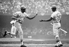 Bob Gibson is congratulated by Lou Brock at home plate.  Gibson home run?  Very possible.