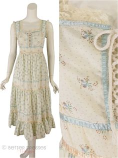 Late 70s or very early 80s boho sundress in cream with tiny blue floral. Sleeveless cotton sundress features corset-style bodice, lace trim, and tiered full A-line skirt. Self ties at sides of waist f
