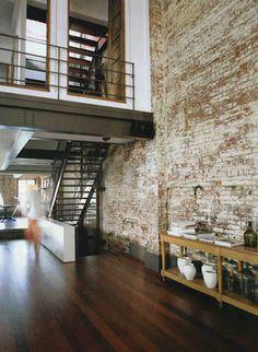 hardwood floor with exposed brick wall