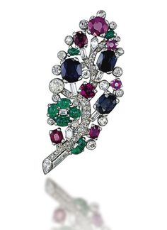 he pavé-set diamond stem decorated with cabochon emeralds, cushion-shaped sapphires and rubies, to the circular-cut diamond collet detail, 1930s, 6.2 cm, with French assay mark for platinum Signed Cartier Paris, no. L2013