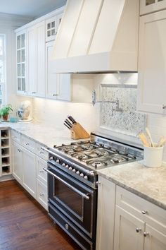 white kitchen with Vermont white granite, white shaker cabinets and Bertazzoni Heritage Collection Range.