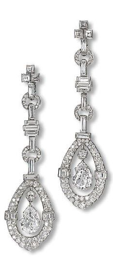 AN ATTRACTIVE PAIR OF ART DECO DIAMOND EAR PENDANTS  Each designed as a pear-shaped diamond pendant within a pavé-set and baguette-cut diamond surround to the baguette-cut diamond line surmount, circa 1920, 7.5 cm long, in grey leather case