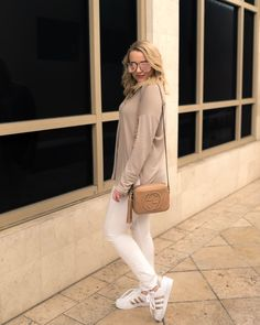 How To Style Adidas Superstar Sneakers - The Fancy Things. Beige long sleeve+white skinny jeans+white sneakers with gold details+camel Gucci tassel crossbody bag+sunglasses. Spring Casual Outfit 2017