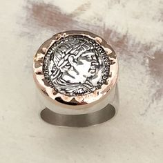 A signet style ring with a Roman relief coin symbol. Beautifully framed by a copper rim. Unique silver rings, earrings, bracelets and necklaces. Unique Silver Rings, Unique Jewelry, Silver Jewellery, Sterling Silver Jewelry, Signet Ring, Jewelry Collection, Artisan, Band, Earrings