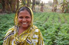 Hazara Bibi, a Trickle Up participant from India, poses for a photo in front her vegetable garden.