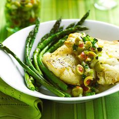 Baked Mediterranean Cod and Asparagus | Team this lean, firm saltwater whitefish with tender asparagus spears, and top with a tangy chopped green olive and caper relish. The cod and asparagus cook together in only 12 minutes.