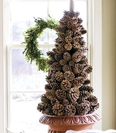 """Pinecone Tree: Create a pinecone tree on a cone-shaped foam base. Anchor the base in a container with a heavy object, then wire the cones onto 2"""" wooden floral picks. Insert picks downward into the foam, starting at the bottom with the largest cones and working to the top with the smaller ones. Conceal the foam by tucking sheet moss among the pinecones."""