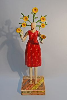 Sunflower Woman by Elizabeth Frank. Sunflower Woman is carved from found aspen branches that the artist collected in the mountains of Arizona and New Mexico.The base is made with vintage crates and yardsticks. The surface of the piece is delicately painted with acrylic and finished with wax. The piece comes apart for shipping and requires simple assembly.
