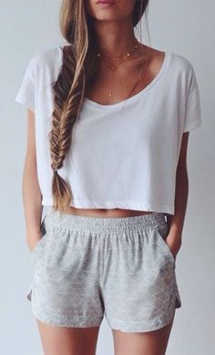 Lazy summer outfit with the white crop top, light grey shorts, messy braids, and layered necklaces
