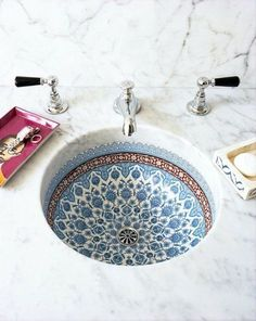 I love this combo of a porcelain sink with delicate patterns and a thick marble countertop. Beautiful, and somewhat within the reach of those of us on not-millionaire budgets.