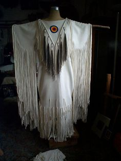 White elk hide dress suede side out with beaded rosette, horse hair tassels bone hair pipe, glass beads and tin cones all hand sewn and stitched