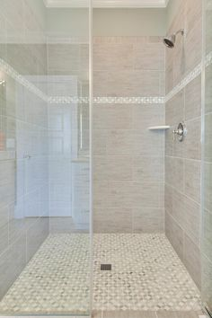 smaller tiles in a criss cross pattern cover the floor and the thin accent strip on the shower wall