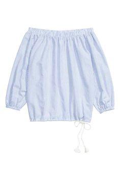 Blouse épaules nues: Blouse épaules nues en coton tissé aérien. Modèle avec bord élastique en haut et en bas des manches longues. Liens de serrage à la base terminés par pompons décoratifs.