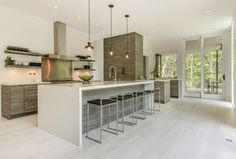 Modern Kitchen with Undermount sink, Pendant Light, Stainless steel modern counter stool, L-shaped, Limestone counters, Flush
